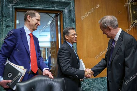 Health and Human Services Secretary Xavier Becerra, center, is greeted by Sen. Ron Wyden, D-Ore., chair of the Senate Finance Committee, left, and Sen. Mike Crapo, R-Idaho, right, the ranking member, as he arrives to testify on President Joe Biden's budget request, at the Capitol in Washington