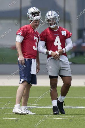 Dallas Cowboys quarterbacks Dak Prescott (4) and Garrett Gilbert (3) talk on the field during an NFL football team practice, in Frisco, Texas