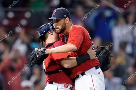 Boston Red Sox closer Matt Barnes, right, hugs catcher Christian Vazquez after the Red Sox's 12-8 victory over the Houston Astros in a baseball game at Fenway Park, in Boston