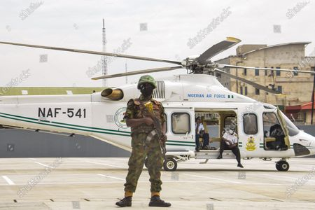 A man of the Nigerian Army stands guard, guarding a helicopter President Buhari came in, at Mobolaji Johnson Railway Station in Ebutemeta, Lagos, Nigeria, on June 10, 2021. President Muhammadu Buhari on Thursday visited Lagos for the inauguration of the 157-kilometer Lagos-Ibadan standard rail project at the Mobolaji Johnson railway station in Ebutte Metta. The Construction which started in March 2017, and test-running commenced in December 2020. The Ebute Metta Station, known as the Mobolaji Johnson Station, is the largest railway station in West Africa with a holding capacity of 6000 passengers A statement from the precedential aide ''''Femi Adesina''.  ''President Buhari is committed to developing a modern national railway network that will connect every part of Nigeria, and promote trade, travel, tourism, commerce and national integration.''