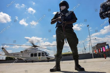 A man of the NigerianPolice stands guard, guarding a helicopter conveying the President Buhari and Lagos State Governor, Babajide Sonwo-Olu, at Mobolaji Johnson Railway Station in Ebutemeta, Lagos, Nigeria, on June 10, 2021. President Muhammadu Buhari on Thursday visited Lagos for the inauguration of the 157-kilometer Lagos-Ibadan standard rail project at the Mobolaji Johnson railway station in Ebutte Metta. The Construction which started in March 2017, and test-running commenced in December 2020. The Ebute Metta Station, known as the Mobolaji Johnson Station, is the largest railway station in West Africa with a holding capacity of 6000 passengers A statement from the precedential aide ''''Femi Adesina''.  ''President Buhari is committed to developing a modern national railway network that will connect every part of Nigeria, and promote trade, travel, tourism, commerce and national integration.''