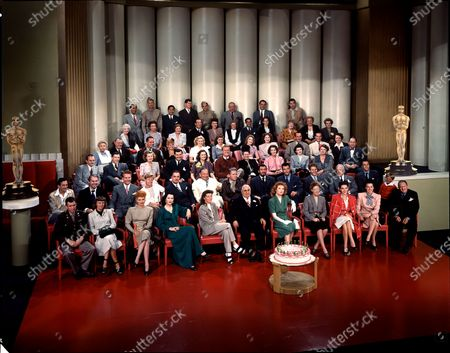 Portrait of Polish-born American film executive and studio head Louis B. Mayer (1885 - 1957) (front row, center, in black suit and eyeglasses), as he poses for a group portrait with movie stars and others at his MGM Studios (Metro Goldwyn Mayer) 20th anniversary, Hollywood, California, 1943. Among those pictured are, front row, from left, James Stewart (1908 - 1997), Margaret Sullavan (1909 - 1960), Lucille Ball (1911 - 1989), Hedy Lamarr (1914 - 2000), Katharine Hepburn (1907 - 2003), Mayer, Greer Garson (1904 - 1996), Irene Dunne (1898 - 1990), Susan Peters (1921 - 1952), Ginny Sims (1915 - 1994), and Lionel Barrymore (1878 - 1954); second row: Harry James (1916 - 1983), Brian Donlevy (1901 - 1972), Red Skelton (1913 - 1997), Mickey Rooney, William Powell (1892 - 1984), Wallace Beery (1885 - 1949), Spencer Tracy (1900 - 1967), Walter Pidgeon (1897 - 1984), Robert Taylor (1911 - 1969), French actor Jean Pierre Aumont (1911 - 2001), Lewis Stone (1879 - 1953), Gene Kelly (1912 - 1996), and Jackie Jenkins (1937 - 2001).