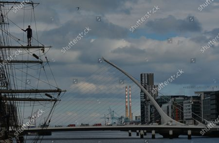 Stock Picture of A young man prepares to jump from the Jeanie Johnston ship into the Liffey River in Dublin.On Thursday, 10 June 2021, in Dublin, Ireland.