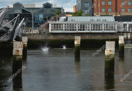 Young boys jump from a roof of a building into the Liffey River in Dublin.On Thursday, 10 June 2021, in Dublin, Ireland.