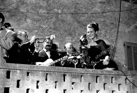 Twenty-four year old French actress Marina Vlady stands on a balcony with a band, a statuette in her hand, an celebrates her birthday with a band during the Cannes Film Festival, Cannes, France, May 10, 1962. The following year won the festival's best actress award.