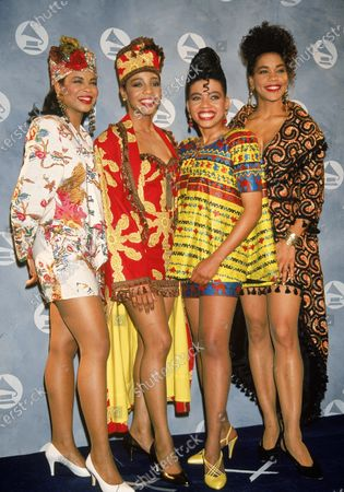 Portrait of popular rhythm and blues vocal group En Vogue as they pose in colorful outfits backstage at the Grammy Awards ceremony in Radio City Music Hall, New York, New York, February 20, 1991. They are, from left, American singers Dawn Robinson, Terry Ellis, Maxine Jones, and Cindy Herron.