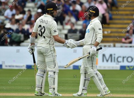 New Zealand's Will Young, left, congratulates batting partner Devon Conway on scoring fifty runs during the second day of the second cricket test match between England and New Zealand at Edgbaston in Birmingham, England