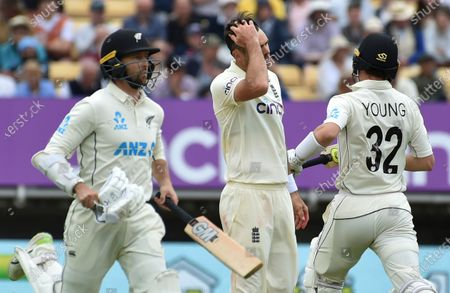 England's James Anderson, center, reacts as New Zealand's Devon Conway, left, and Will Young run between the wickets to score during the second day of the second cricket test match between England and New Zealand at Edgbaston in Birmingham, England