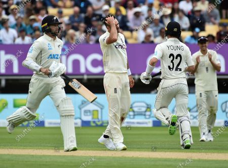 England's James Anderson, second left, reacts as New Zealand's Devon Conway, left, and Will Young run between the wickets to score during the second day of the second cricket test match between England and New Zealand at Edgbaston in Birmingham, England