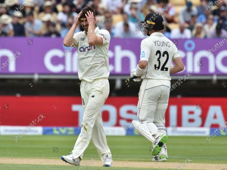 England's Mark Wood, left, reacts after bowling a delivery as New Zealand's Will Young runs between the wickets to score during the second day of the second cricket test match between England and New Zealand at Edgbaston in Birmingham, England