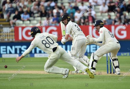 England's Ollie Pope, left, attempts to field the ball after a shot played by New Zealand's Will Young, center, during the second day of the second cricket test match between England and New Zealand at Edgbaston in Birmingham, England