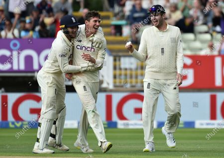 England's Dan Lawrence, center, celebrates with teammates the dismissal of New Zealand's Will Young during the second day of the second cricket test match between England and New Zealand at Edgbaston in Birmingham, England