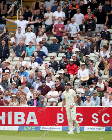 James Anderson of England stands in front of the Hollies Stand as the fans sing his name