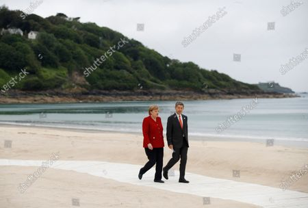 German Chancellor Angela Merkel (L) and her spouse Joachim Sauer arrive for the G7 summit in Carbis Bay, Cornwall, Britain, 11 June 2021.