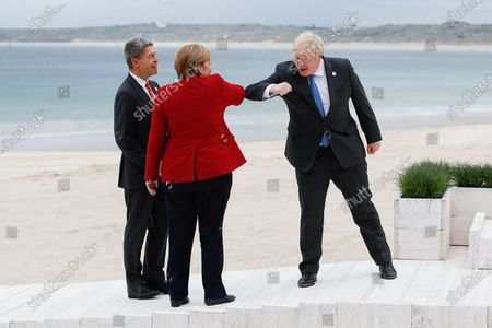 Britain's Prime Minister Boris Johnson (R) greets German Chancellor Angela Merkel (C) and her spouse Joachim Sauer (L) during the G7 summit in Carbis Bay, Cornwall, Britain, 11 June 2021.