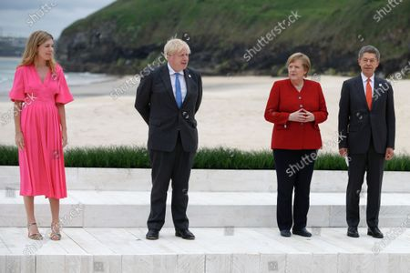 Britain's Prime Minister Boris Johnson (2-L) and his spouse Carrie Johnson (L) pose with German Chancellor Angela Merkel (2-R) and her spouse Joachim Sauer (R) during the G7 summit in Carbis Bay, Cornwall, Britain, 11 June 2021.