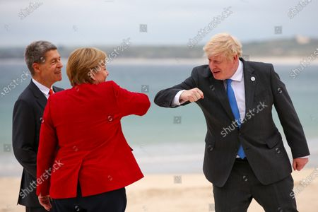Boris Johsnon, U.K. prime minister, elbow bumps Angela Merkel, Germany's chancellor, and her husband Joachim Sauer, on the first day of the Group of Seven (G7) leaders summit in Carbis Bay, Cornwall, Britain, 11 June 2021. Britain hosts the G7 summit in Cornwall in from 11 to 13 June 2021.