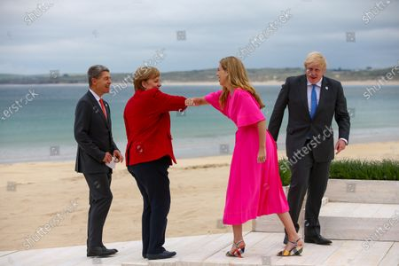 Carrie Johnson, wife of U.K. Prime Minister Boris Johnson, second right, elbow bumps Angela Merkel, Germany's chancellor, second left, as Boris Johsnon, U.K. prime minister, and Joachim Sauer, husband of German Chancellor Angela Merkel, on the first day of the Group of Seven (G7) leaders summit in Carbis Bay, Cornwall, Britain, 11 June 2021. Britain hosts the G7 summit in Cornwall in from 11 to 13 June 2021.