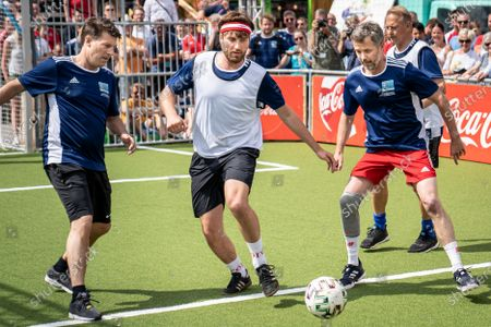 Stock Photo of Denmark's Crown Prince Frederik (R), Danish former soccer player Michael laudrup (L), and Danish musician Malte Ebert (C) participate in a show match during the opening of the UEFA Euro 2020 fan zone 'Football Village' at Ofelia Plads in Copenhagen, Denmark, 11 Friday June 2021.