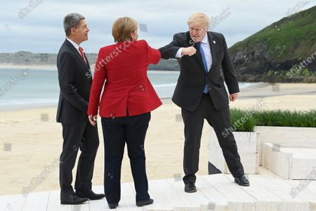 German Chancellor Angela Merkel accompanied by her husband, Joachim Sauer, bumps elbows with British Prime Minister Boris Johnson at the Carbis Bay Hotel on June 11, 2021, during the G7 summit in Cornwall, United Kingdom.