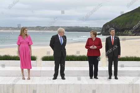 Britain's Prime Minister Boris Johnson, centre left and wife Carrie Johnson, left, pose with German Chancellor Angela Merkel, and her husband Joachim Sauer for the Leaders official welcome and group photo session, during the G7 summit, in Carbis Bay, Cornwall, England