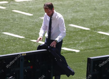 England manager Gareth Southgate removes his suit jacket as temperatures soar