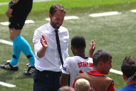 England manager Gareth Southgate celebrates on the final whistle with Raheem Sterling