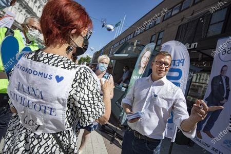 Petteri Orpo (R), chairman of The National Coalition Party, talks with other candidates and actives of the party during municipal elections campaign event in Turku, Finland, on June 11, 2021.