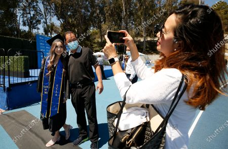 """Graduating with a degree in Communication Studies and Business/Economics, Maddie Park poses with her Father Richard Park as Mom Stephanie Park takes a photo as graduating UCLA students walk the stage in Drake Stadium while their names are announced with their image on a video monitor and pose for official photographs as they take part in a """"Graduation Celebration."""" Up to 230 students per hour will participate in the graduate procession through Drake Stadium each day for six days with up to one student every 15 seconds. More than 9,000 students over six days starting Thursday before and after a virtual ceremony on Friday night, will walk through Drake Stadium with up to two guests to get the graduation experience of crossing a real stage as their names are read. Roughly 14,000 undergraduates and graduate students total are expected to receive their degrees from UCLA this year. UCLA on Thursday, June 10, 2021 in Los Angeles, CA. (Al Seib / Los Angeles Times)."""
