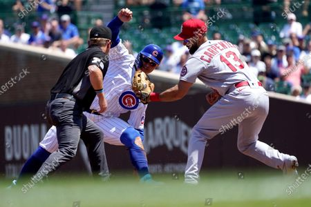 St. Louis Cardinals' Matt Carpenter (13) shows second base umpire Mike Muchlinski the ball after catching Chicago Cubs' Joc Pederson trying to steal second during the first inning of a baseball game, in Chicago