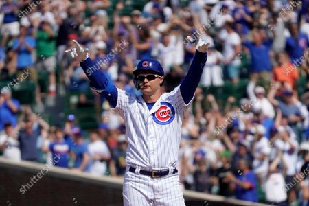 Chicago Cubs' Joc Pederson looks around Wrigley Field and celebrates his two-run double off St. Louis Cardinals relief pitcher Genesis Cabrera during the seventh inning of a baseball game, in Chicago
