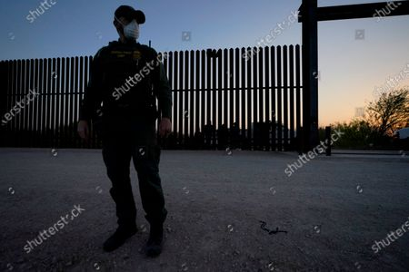 A U.S. Customs and Border Protection agent looks on near a gate on the U.S.-Mexico border wall as agents take migrants into custody, in Abram-Perezville, Texas. Texas Gov. Greg Abbott has has offered scarce details on his plans to construct new barrier along the border with Mexico. It remained unclear Friday, June 11 on how much barrier Texas would erect or where or when it would be installed on the state's 1,200-mile border with Mexico