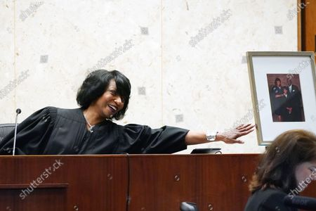"""New U.S. District Chief Judge Debra M. Brown, reaches towards a family portrait of herself and her parents as she speaks about becoming the Chief Judge, during a """"gavel passing ceremony"""" in Greenville, Miss., . Brown made history when she became Mississippi's first female African American U.S. District Judge after being appointed by President Barack Obama in 2013, and she becomes the eighth Chief Judge for the Northern District of Mississippi and the first African American female Chief Judge in Mississippi"""
