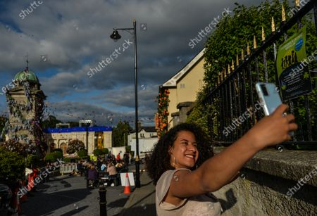 A visitor takes a selfie inside the village of Enniskerry in County Wicklow. There are only two more days until filming begins for Disney's 'Disappointed,' starring Amy Adams, Patrick Dempsey, James Marsden, Idina Menzel and Maya Rudolph.A team of carpenters, painters, builders and decorators put the finishing touches to make parts of the village look like a magical Disney wonderland.On Friday, 11 June 2021, in Enniskerry, County Wicklow, Ireland.