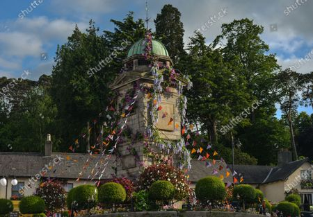Stock Photo of The Clock Tower decorated with flowers in the village of Enniskerry in County Wicklow. There are only two more days until filming begins for Disney's 'Disappointed,' starring Amy Adams, Patrick Dempsey, James Marsden, Idina Menzel and Maya Rudolph.A team of carpenters, painters, builders and decorators put the finishing touches to make parts of the village look like a magical Disney wonderland.On Friday, 11 June 2021, in Enniskerry, County Wicklow, Ireland.