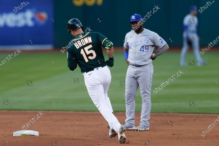 Oakland Athletics Seth Brown (L) rounds second base after hitting a two-run home run ball off Kansas City Royals starting pitcher Brady Singer as Kansas City Royals shortstop  Hanser Alberto (R) looks on during the fourth inning of their MLB game at RingCentral Coliseum in Oakland, California, USA, 11 June 2021.