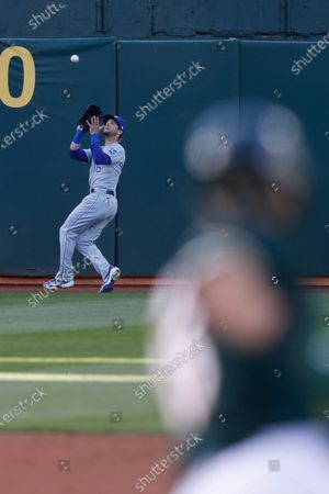 Kansas City Royals left fielder Andrew Benintendi (L) chases down a fly ball by Oakland Athletics Seth Brown (R) during the second inning of their MLB game at RingCentral Coliseum in Oakland, California, USA, 11 June 2021.