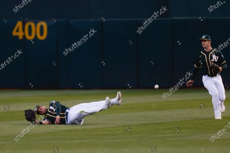 Oakland Athletics center fielder Mark Canha (R) and Oakland Athletics right fielder Seth Brown (L) unable to catch a ball hit by Kansas City Royals Jorge Soler for a single during the seventh inning of the MLB baseball game between the Kansas City Royals and the Oakland Athletics at RingCentral Coliseum in Oakland, California, USA, 11 June 2021.