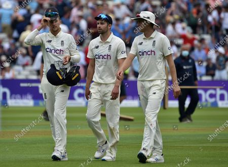 England captain Joe Root, left, walks off the field with teammates Mark Wood, center, and Olly Stone at lunch during the third day of the second cricket test match between England and New Zealand at Edgbaston in Birmingham, England