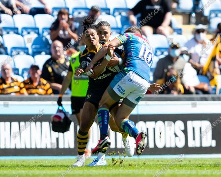 Marcus Watson, making his first home appearance of the season for Wasps, is tackled by Johnny McPhillips of Leicester Tigers