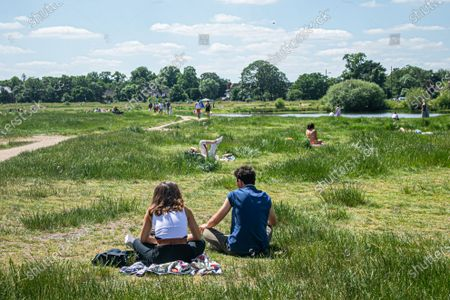 People relax in the sunshine on Wimbledon Common on a hot day in London  as temperatures are predicted to reach 30C  this weekend, with the warmest day of the year expected