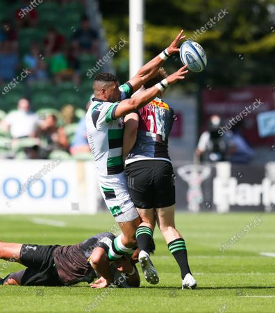Luther Burrell of Newcastle offloads while being tackled by Louis Lynagh of Harlequins