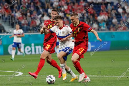 Russia's Aleksandr Golovin, center, is flanked by Belgium's Leander Dendoncker, left, and Belgium's Timothy Castagne during the Euro 2020 soccer championship group B match between Belgium and Russia at the Saint Petersburg stadium in St. Petersburg, Russia