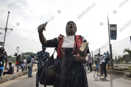 A female preacher holding Holy Bible eco slogans during civil demonstration at the Gani Fahweyinmi Park, Ojota district of Lagos, Nigeria, venue of the June 12 protest, on 12 June 2021.Nigerian police on June 12, 2021 fired tear gas to disperse anti-government protesters in Lagos and the capital, Abuja, arresting many while others were injured. Many activists had called for nationwide protests on Saturday on June 12 'Democracy Day', which marks Nigeria's move to civilian rule more than 20 years ago, over what they criticise as bad governance and insecurity, as well as the recent #Twitter ban by the current government of President Muhammadu Buhari.