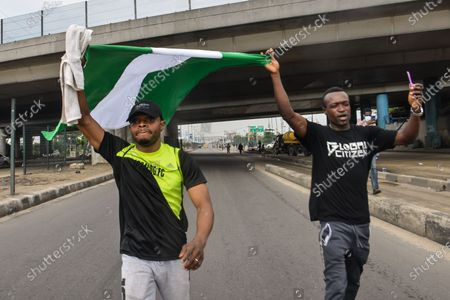 Porters holds a Nigerian flag during civil demonstration at the Gani Fahweyinmi Park, Ojota district of Lagos, Nigeria, venue of the June 12 protest, on 12 June 2021.Nigerian police on June 12, 2021 fired tear gas to disperse anti-government protesters in Lagos and the capital, Abuja, arresting many while others where injured. Many activists had called for nationwide protests on Saturday on June 12 'Democracy Day', which marks Nigeria's move to civilian rule more than 20 years ago, over what they criticise as bad governance and insecurity, as well as the recent #Twitter ban by the current government of President Muhammadu Buhari.