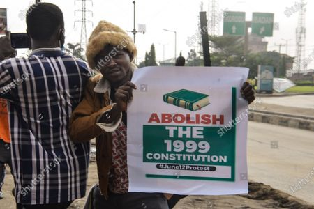 A protester holds a banner during civil demonstration at the Gani Fahweyinmi Park, Ojota district of Lagos, Nigeria, venue of the June 12 protest, on 12 June 2021.Nigerian police on June 12, 2021 fired tear gas to disperse anti-government protesters in Lagos and the capital, Abuja, arresting many while others were injured. Many activists had called for nationwide protests on Saturday on June 12 'Democracy Day', which marks Nigeria's move to civilian rule more than 20 years ago, over what they criticise as bad governance and insecurity, as well as the recent #Twitter ban by the current government of President Muhammadu Buhari.