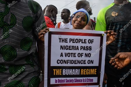 A female protester holds a banner during civil demonstration at the Gani Fahweyinmi Park, Ojota district of Lagos, Nigeria, venue of the June 12 protest, on 12 June 2021.Nigerian police on June 12, 2021 fired tear gas to disperse anti-government protesters in Lagos and the capital, Abuja, arresting many while others were injured. Many activists had called for nationwide protests on Saturday on June 12 'Democracy Day', which marks Nigeria's move to civilian rule more than 20 years ago, over what they criticise as bad governance and insecurity, as well as the recent #Twitter ban by the current government of President Muhammadu Buhari.