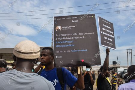 Stock Image of Protesters hold banners during civil demonstration at the Gani Fahweyinmi Park, Ojota district of Lagos, Nigeria, venue of the June 12 protest, on 12 June 2021.Nigerian police on June 12, 2021 fired tear gas to disperse anti-government protesters in Lagos and the capital, Abuja, arresting many while others were injured. Many activists had called for nationwide protests on Saturday on June 12 'Democracy Day', which marks Nigeria's move to civilian rule more than 20 years ago, over what they criticise as bad governance and insecurity, as well as the recent #Twitter ban by the current government of President Muhammadu Buhari.