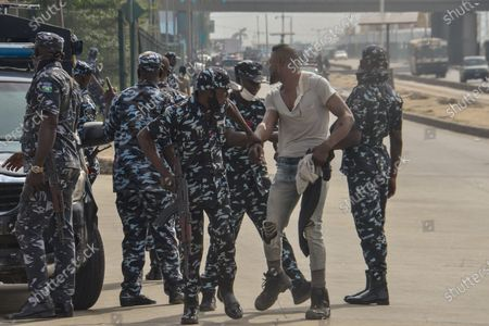 Stock Photo of Policemen arrested a protester during civil demonstration at the Gani Fahweyinmi Park, Ojota district of Lagos, Nigeria, venue of the June 12 protest, on 12 June 2021.Nigerian police on June 12, 2021 fired tear gas to disperse anti-government protesters in Lagos and the capital, Abuja, arresting many while others were injured. Many activists had called for nationwide protests on Saturday on June 12 'Democracy Day', which marks Nigeria's move to civilian rule more than 20 years ago, over what they criticise as bad governance and insecurity, as well as the recent #Twitter ban by the current government of President Muhammadu Buhari.