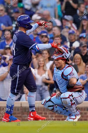Stock Photo of Chicago Cubs' Joc Pederson, left, celebrates after hitting a solo home run as St. Louis Cardinals catcher Yadier Molina looks to the field during the fourth inning of a baseball game in Chicago